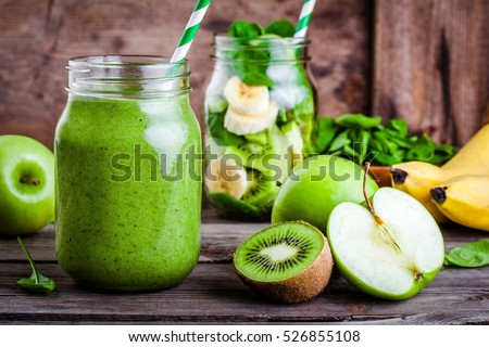 Green healthy  smoothie in  glass jar: banana, kiwi, spinach, green apple on rustic background