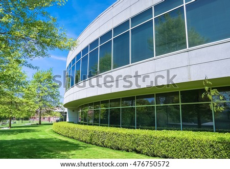 Green hedge and mowed lawn along round shaped wall of the office building #476750572