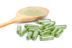 Green herbal powder capsule and dried leaf plant powder in wooden spoon isolated on white background.