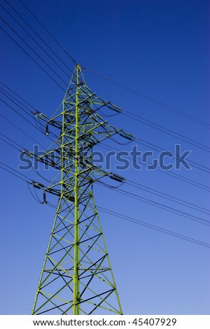 Green high voltage electric line against blue sky