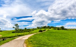 Green hill path sky clouds. Rad to green hill. Green hill road landscape