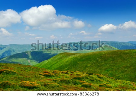 green hills and blue sky with clouds in Carpathian mountains - stock photo