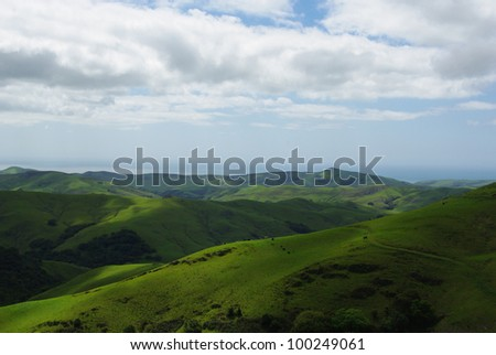 Green hills and pastures with view on Pacific Ocean, California