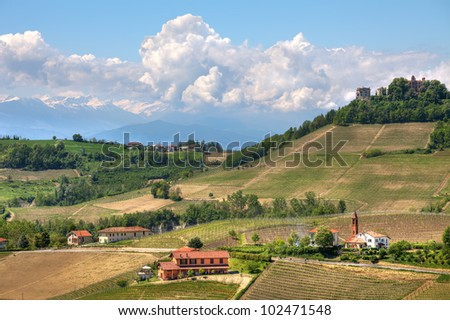 Green hills and vineyards and mountains on the background at spring in Piedmont, Northern Italy.