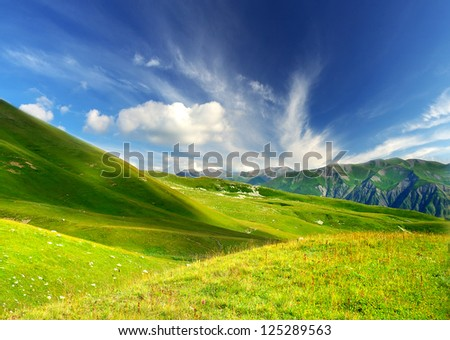Green hills in mountain valley. Summer landscape - stock photo
