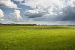 Green hills of a plowed agricultural field and forest. Idyllic summer rural scene. Dramatic sky, rain, thunderstorm. Pure nature, environnement, farm, countryside living, ecotourism. Panoramic view