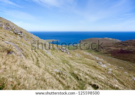 Green hills overlooking the sea at Barra . Landscape of Outer Hebrides, Scotland .