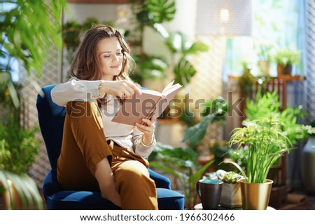 Green Home. relaxed trendy middle aged woman with long wavy hair with book in green pants and grey blouse in the modern living room in sunny day.