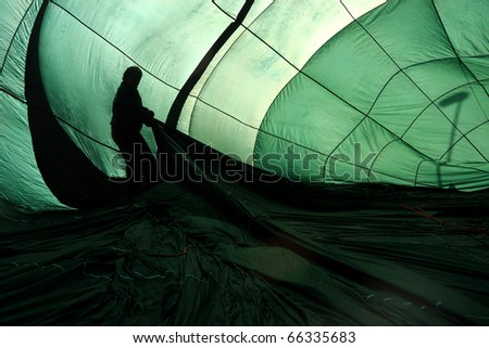 Green hot air balloon being inflated with silhouette of pilot in the interior
