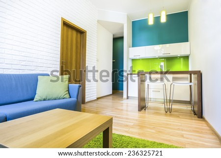 Green hotel room with sofa and kitchenette