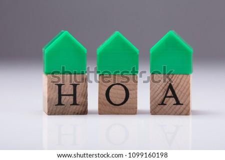 Green House Model Over Homeowner Association Wooden Blocks #1099160198