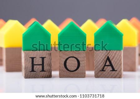 Green House Model Over Homeowner Association Wooden Blocks #1103731718