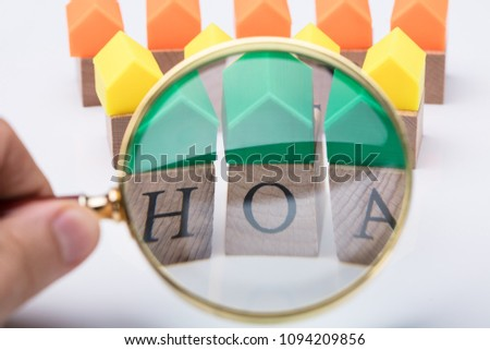 Green House Model Over Homeowner Association Wooden Blocks Seen Through A Person Holding Magnifying Glass #1094209856
