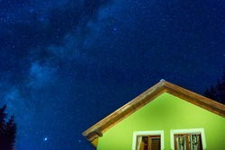 Green house under dark blue night sky with many stars, cosmos milky way background
