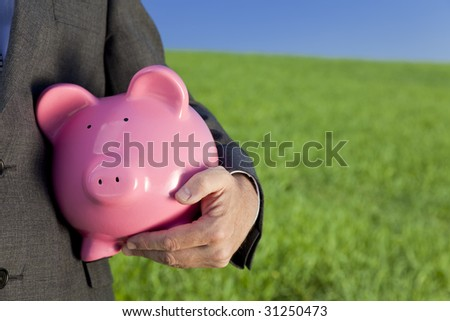 Green investment concept shot of a man in a suit holding a big pink piggy bank in a green field with a bright blue sky. Shot on location with the focus on the piggy bank in the foreground.