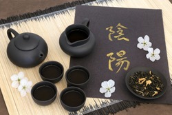 Green jasmine tea with yin and yang chinese calligraphy script, teapot, cups, dried leaves and cherry blossom on bamboo mat. Translation reads as yin yang.