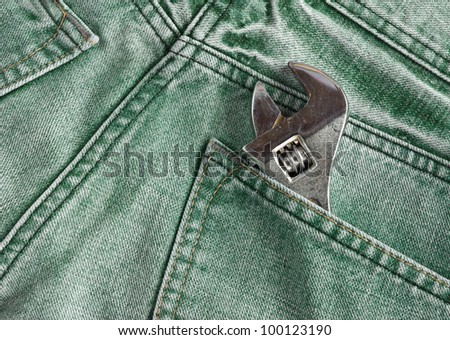 Green jeans pocket with old tool