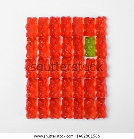 Green jelly bear among red ones on white background, top view. Individuality concept