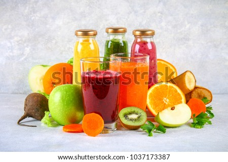 Green juice, yellow juice, purple smoothies in currant bottles, parsley smoothie, apple juice, kiwi smoothie, orange juice on a gray table. Orange and purple smoothies in glasses of beet and carrots