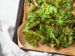 Green Kale Chips with salt on oven-tray. Homemade healthy snack for low carb, keto, low calorie diet. Gray cement background. Ready-to-eat kale chips, copy space for text