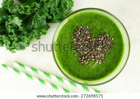 Green kale smoothie downward view in glass with heart shape made of healthy chia seeds