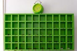 Green key storage box with clock on it. Check in at reception desk.