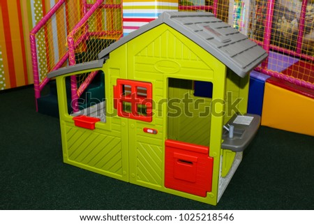 Green kids playhouse in the entertainment center. Plastic children play house with red and orange door and window. Green floor. Joy and fun. Playing games.