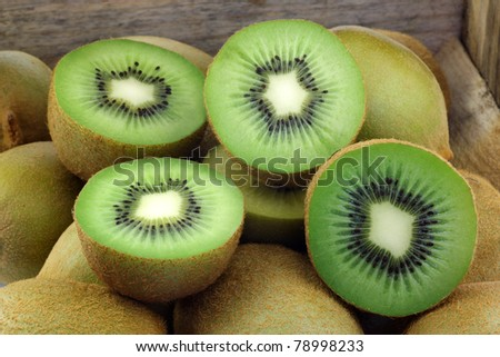 green kiwi fruit and some cut ones in a wooden box