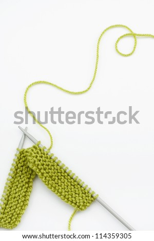 Green knitting wool and knitting needles