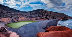 Green lake El Golfo on Lanzarote in Canary islands. There is black beach and blueocean.