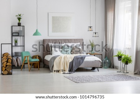 Green lamp above retro chair next to bed against the wall with silver painting in spacious bedroom interior
