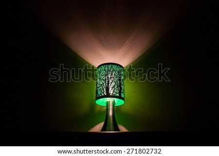 Green lamp with a tree design lighting up a wall at night surrounded by dark shadows.