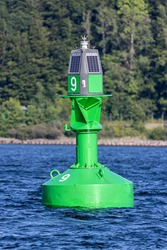green lateral buoy at the edge of a fairway