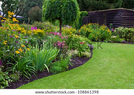 Green lawn in a colorful landscaped formal garden. Beautiful Garden.