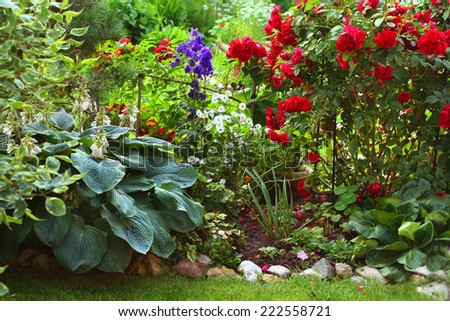Green lawn in a colorful landscaped formal garden. Beautiful Garden