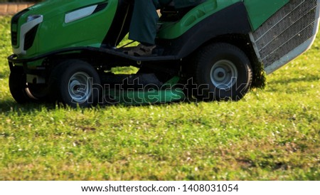 Green lawn mower cutting grass close up. Man cutting the grass with electric lawn mower on sunny day, cropped image. #1408031054