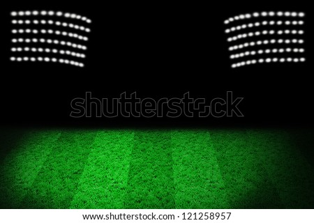 Green lawn of a football field with stadium light