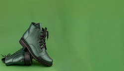 Green leather shoes banner. Winter and spring off-season boots. Stylish boot isolated on background. Close-up. Laces, tractor sole. Casual style. Copy space. Pearlescent fashionable color.