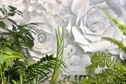 Green leaves and different white hand made paper flowers decorative wall design