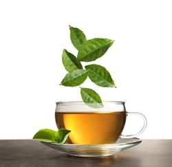 Green leaves falling into cup of tea on table against white background