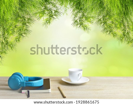 Green leaves of bamboo It is on top and the bokeh is visible. On the table, place a cup of coffee, tablet, blue music headphones, diary and notebooks to record. Feelings, sadness, loneliness, nostalgi Photo stock ©