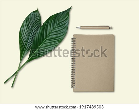 Green leaves of peace lily - spathiphyllum, paper notebook and wooden pen on yellow background. Eco friendly workspace concept. Overhead view. Foto stock ©