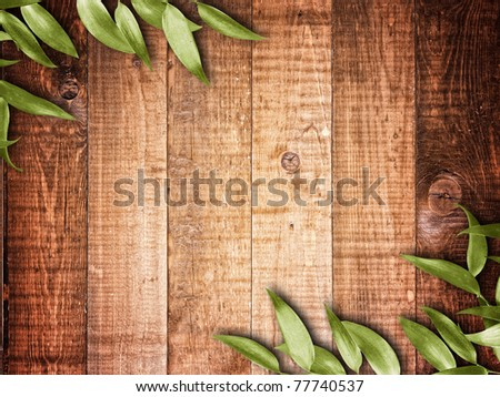 green leaves on the old wooden background