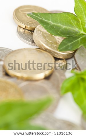 Green leaves placed on various types of coins.