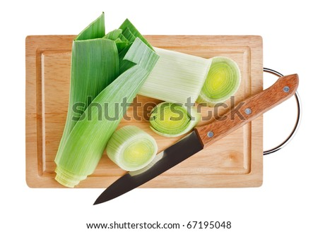 Green leek with knife on wooden chopping board over white background