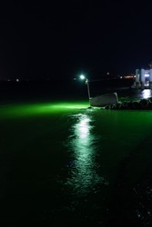 Green light shining in the ripples of the ocean, strange, odd, give it a story. Tamsui, New Taipei City, Night.