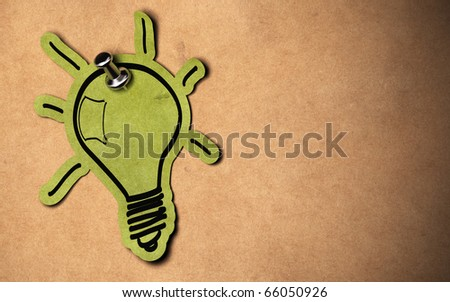 green lightbulb concept, paper bulb fixed on a kraft paper background with copy space