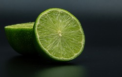 Green lime citruss fruit cutting half macro fiber inside, black background