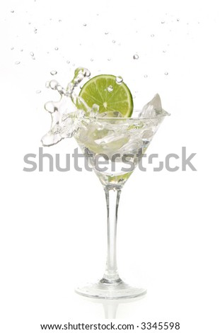 Green lime splashing into a martini glass