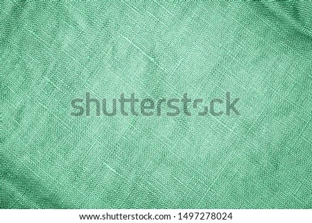 Green linen fabric background. COLOR TREND 2020 Neo mint. Abstract new mint color background. Seafoam Green linen cloth texture. Wrinkled pure linen fabric background. Natural green  linen texture